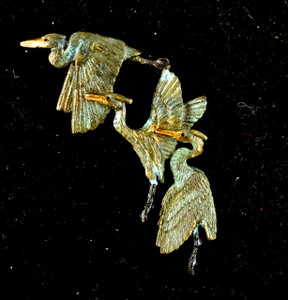 "Cavin Richie design three herons pin, cast in lightweight artist's bronze, 1.8 X 1.8"".  Herons are shown in standing, rising, and flying positions. Casting was created from one of Cavin's original shed-elk antler or  woolly mammoth ivory carvings, to give the finished product more natural detail than is possible with a wax carving. Cast in the USA and hand finished in Washington State."