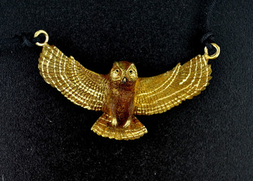 The great horned owl is shown sweeping down on its prey in this Cavin Richie designed pendant, with beautiful detail on both sides. The size is 1 inch high and 2 inches wide, cast in lightweight artist's bronze.  The fabric cord is adjustable from 18 to 36 inches. Casting was created from one of Cavin's original shed-elk antler or woolly mammoth ivory carvings, to give the finished product more natural detail than is possible with a wax carving. Cast in the USA and hand finished in Washington State.