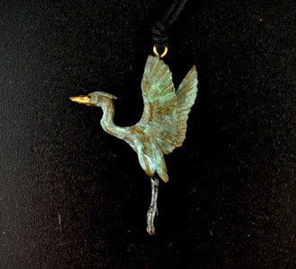 "With a wingspan of nearly six feet, the power of a rising great blue heron comes to life in this Cavin Richie design, cast in lightweight artist's bronze, 1.9"" X 1.5"". The fabric cord is adjustable from 18 to 36 inches. Casting was created from one of Cavin's original shed-elk antler or  woolly mammoth ivory carvings, to give the finished product more natural detail than is possible with a wax carving. Cast in the USA and hand finished in Washington State."