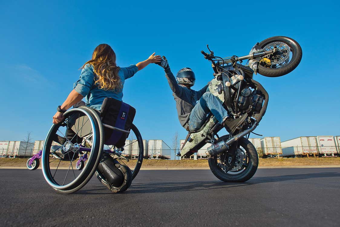 SmartDrive MX2 behind a wheelchair riding a wheelie and giving a motorcycle a high five.