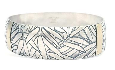 Sterling silver bangle bracelet with 18kt gold and bamboo leaf design.