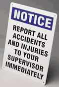 Photograph of notice accident and injury reporting sign in use on floor.