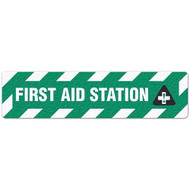 """Photograph of an anti-slip floor safety sign reading """"First Aid Station"""" in white on a green background.  Includes a graphic of a white cross within a black triangle."""