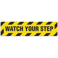 """Photograph of an anti-slip floor safety sign reading """"Watch Your Step"""" in black on a yellow background."""