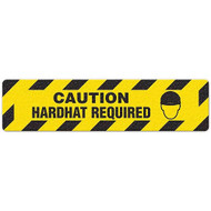 """Photograph of an anti-slip floor safety sign reading """"Caution Hardhat Required"""" in black on a yellow background.  Includes a graphic of a head wearing a hardhat."""