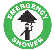 A green and white photograph of a 05223 anti-slip safety floor markers, reading emergency shower with arrow graphic.