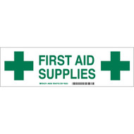 A green and white photograph of a 03416 first aid supplies cabinet label with cross graphics.