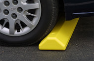 A closeup photograph of a 02260 eagle protective parking stop with car wheel right on it.
