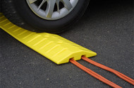 A photograph of a 02264 eagle speed bump/cable protector with a car on top of the bump.