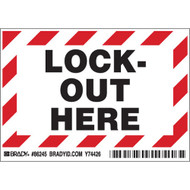 A photograph of a red and white 07019 lock out here peel-and-stick permanent adhesive label.