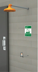A photograph of an orange Guardian GFR1205 Freeze-Resistant Emergency Shower installed in a cinderblock wall.
