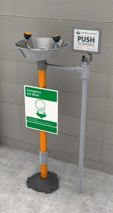 A photograph of a Guardian GFR1825 Freeze-Resistant Eyewash, Pedestal Mounted, Stainless Steel Bowl installed next to a cinderblock wall.