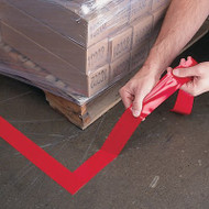 A photograph of red 06435 removable floor tape in use on floor at a facility.