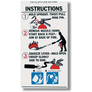 A photograph of a 09964 carbon dioxide fire extinguisher with hose instructional label.