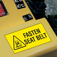 A photograph of a yellow 12205 forklift label, reading fasten seat belt with graphic installed on machinery.