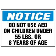 A photograph of a blue and white 13010 AED label reading notice do not use AED on children under 55 lb or 8 years of age.