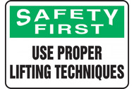 A photograph of a green and white 12309 safety first, use proper lifting techniques sign.