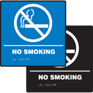 A photograph of a blue and a black 03506 ADA braille tactile sign, reading no smoking with cigarette prohibition graphic.
