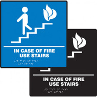 A photograph of a blue and a black 03503 ADA braille tactile sign, reading in case of fire use stairs with person on stairs icon.