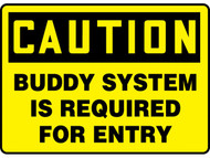 A photograph of a yellow and black 01700 caution buddy system is required for entry OSHA sign.