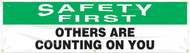 """Picture of Workplace Safety Banner that features a professional white background with green header, and wording """"Safety First"""" in bold white text in the header. Below is the wording """"Others Are Counting On You"""" in serious black text."""