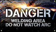 """Picture of Workplace Safety Banner that features  a dark background lit up by sparks, as something is being welded in the background. In front of this in clear large bold white letters the banner reads """"Danger"""". Below in slightly smaller white text it reads """"Welding area do not watch arc""""."""