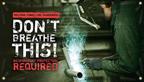 """Picture of Workplace Safety Banner that features a metal workshop as background. In the front is a worker with a face-guard to protect himself welding a piece of metal. There are fumes coming off this welding job. On the left side of the banner there is a red stripe at the top, with words cut out that reads """"Welding fumes are dangerous"""". Below that is large white text that reads """"Don't breathe this!"""". Finally below that in alert red text it reads """"Respiratory protection required""""."""