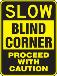 A photograph of a yellow and black 06254 blind corner sign, reading slow blind corner - proceed with caution.