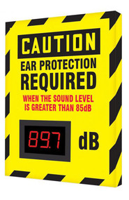 """A photograph of a yellow and black 11104 OSHA caution industrial decibel meter sign, reading ear protection required when the sound level is greater than 85 dB, and dimensions 12"""" l x 10"""" w."""