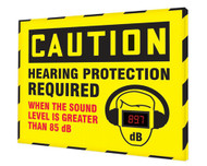 """A photograph of a yellow and black 11105 OSHA caution industrial decibel meter sign, reading hearing protection required when the sound level is greater than 85 dB, and dimensions 30"""" x 36"""" ."""