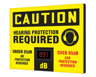 """A photograph of a yellow and black 11107 OSHA caution industrial decibel meter sign, reading hearing protection required, and dimensions 20"""" x 24"""" ."""