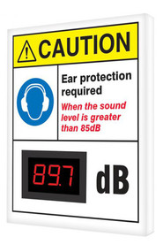 """A photograph of a 11108 OSHA caution industrial decibel meter sign, reading ear protection required when the sound is greater than 85 dB, and dimensions 12"""" x 10""""."""