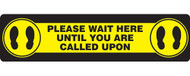 """A photograph of a yellow and black 11201 social distance floor sign, reading please wait here until you are called upon, with dimensions 6"""" x 24"""", and footprint icons."""