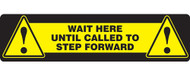 """A photograph of a yellow and black 11202 social distance floor sign, reading wait here until called to step forward, with dimensions 6"""" x 24"""", and alert icons."""