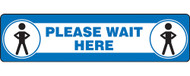 """A photograph of a blue and white 11205 social distance floor sign, reading please wait here, with dimensions 6"""" x 24"""", and person icons."""