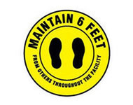 A photograph of a yellow and black 05403 removable social distance floor sign, reading maintain 6 feet from others throughout the facility, with footprints graphics.