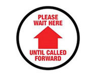 A photograph of a red and white 05405 removable social distance floor sign, reading please wait here until called forward, with arrow icon.