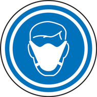 Circular sign with a blue background, white icon of a person wearing a face mask, and two blue and one white circle around the perimeter.