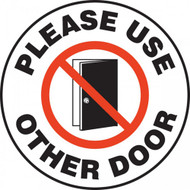 A photograph of a white and black 11257 pavement print sign, reading please use other door, with door graphic.
