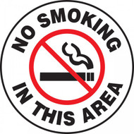 A photograph of a black and white 11258 pavement print sign, reading no smoking in this area, with a no smoking graphic.