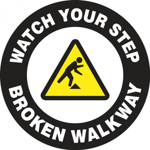 """This black and white sign features a yellow caution sign in the center with the image of a figure tripping over an obstacle. White text on a black border reads """"Watch Your Step, Broken Walkway"""". Use for areas with broken and dangerous walkways."""