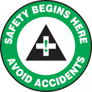 "This green, white, and black sign features the text ""Safety Begins Here Avoid Accidents"". In the center is an ANSI-style safety cross in green and black. Use to promote awareness of safety and accidents."
