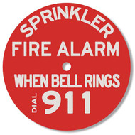"""This red plastic sign  has white lettering that reads """"SPRINKLER FIRE ALARM.  WHEN BELL RINGS DIAL 911."""""""