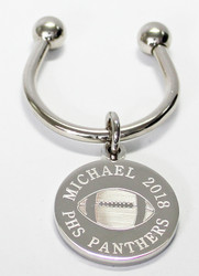 Football keychain.  Made of non tarnish high quality nickel plate.  Beautifully engraved round disk with football graphic and text arched across the top and bottom.  Makes a great gift for football players and coach.  Comes with horseshoe shaped keyring, round split ring keyring, engraved disk and comes boxed in a silver cotton filled gift box.