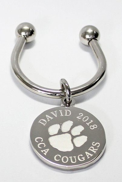 Paw Print keychain.  Made of non tarnish high quality nickel plate.  Beautifully engraved round disk with paw print graphic and text arched across the top and bottom.  Makes a great gift for team players and coach.  Also makes a great gift for teachers retiring or leaving the school.  Comes with horseshoe shaped keyring, round split ring keyring, engraved disk and comes boxed in a silver cotton filled gift box.