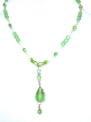 "Light weight and delicate this gracious Green Frosted Glass Pendant is Wrapped in silver Wire and hangs on a gentle strand of Green frosted glass beads with Faceted Crystal accents 16"" @ $65. 20"" @ $68."