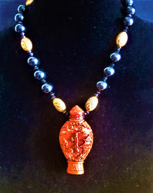 #AN40 A UNIQUE NECKLACE MADE OF A CARVED CHINESE CINNABAR URN AS A PENDANT SUSPENDED A STRAND OF BLACK BEADS AND ENGRAVED GOLD BEADS , URNS LIKE THIS WERE ORIGINALLY USED FOR STORING COCAINE IN CHINA YEARS AGO.