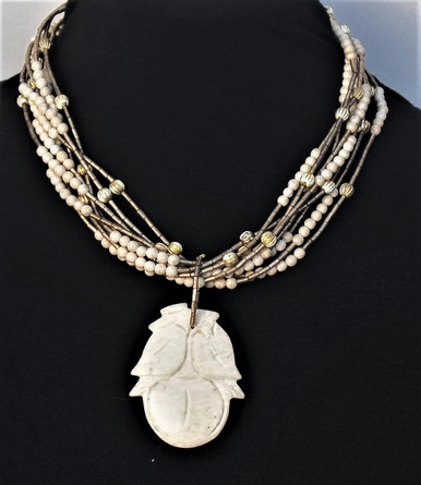 "#AN60 CARVED BEIGE FOSSIL STONE PENDANT HANGING FROM MULTIPLE STRANDS OF FOSSIL STONE AND GOLD BEADS  18"" $165.   20"" $170. 25"" @ $180."