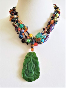 #BN65  ONE OF A KIND CARVED GREEN JADE PENDANT ON MULTIPLE STRANDS OF HAND BLOWN GLASS.  AVAILABLE IN 18 INCHES $755.