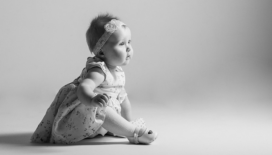 Stunning black and white image of baby in studio. Photograph by Emotion Studios.